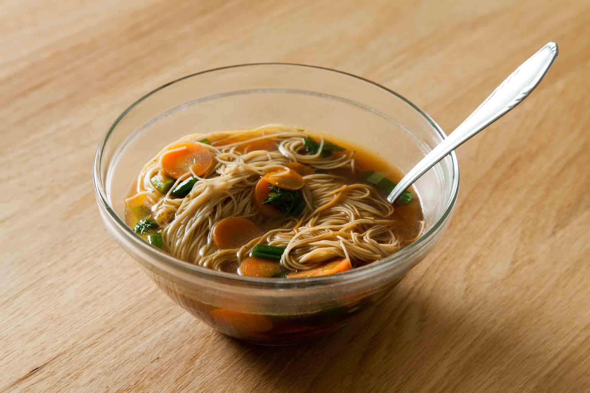 Bistra zelenjavna juha s sojino omako, mlado čebulo, korenjem in polnozrnatimi rezanci